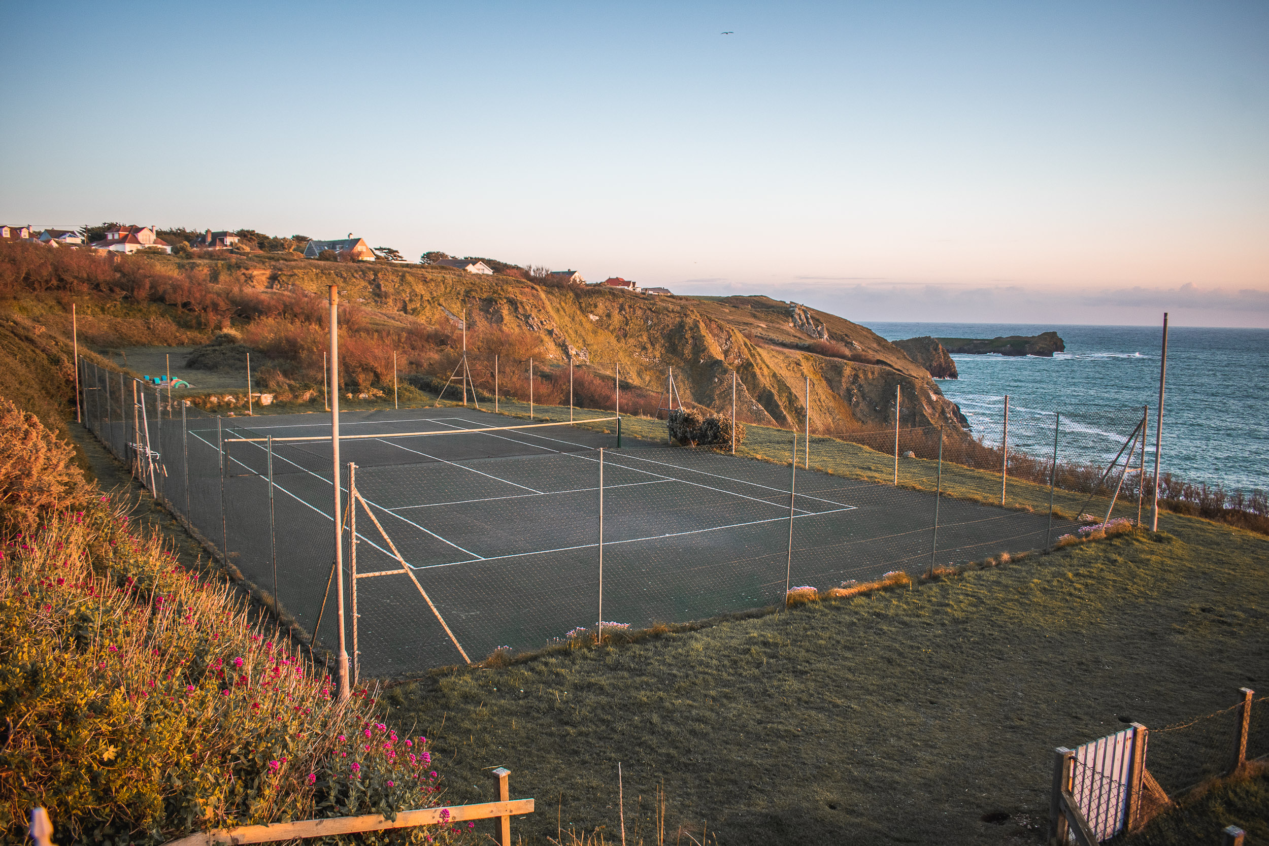 Outdoor tennis courts with a stunning sunset in the background.