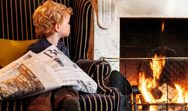 A boy sits in an armchair by the fire at a luxury family hotel