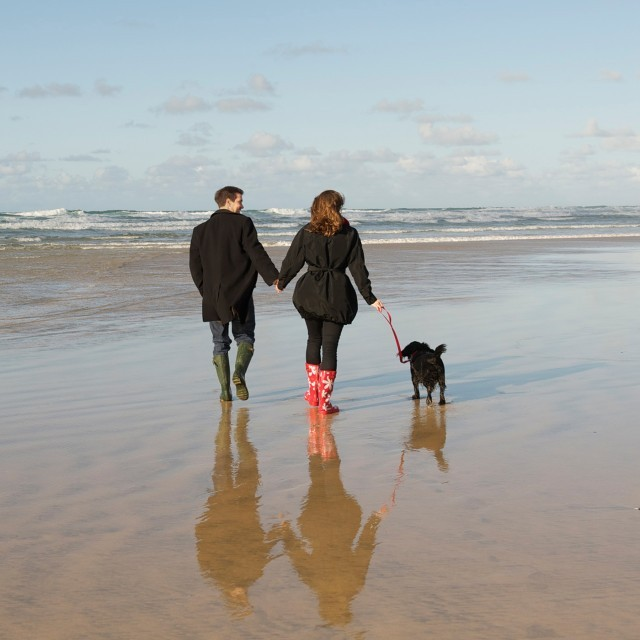 Couple walking their dog on holiday in Cornwall