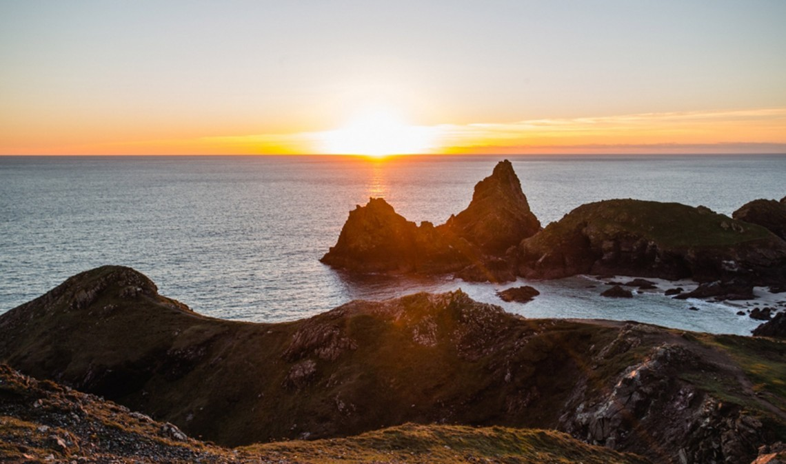 The sun sets behind the sea horizon with islets, sea stacks and the rocky headland in the foreground.