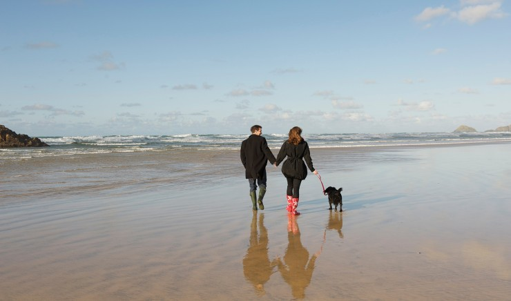 Couple on the beach during a dog-friendly hotel break in Cornwall at the Polurrian Bay Hotel