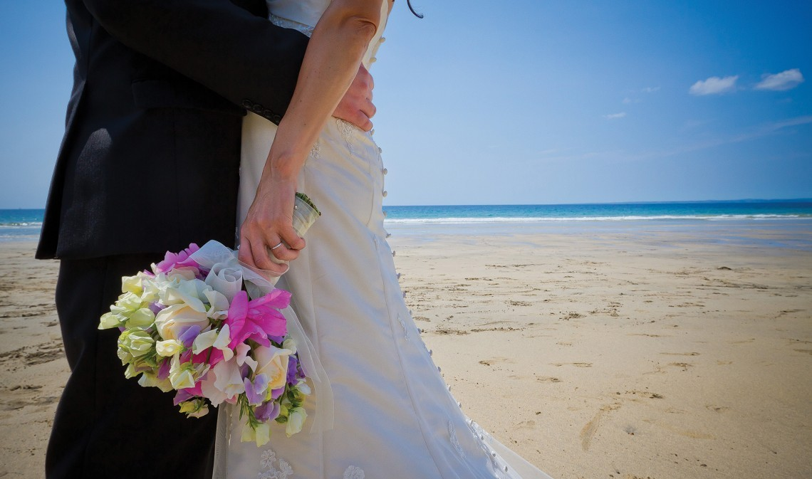 Wedding couple at their Cornwall beach wedding at Polurrian Bay