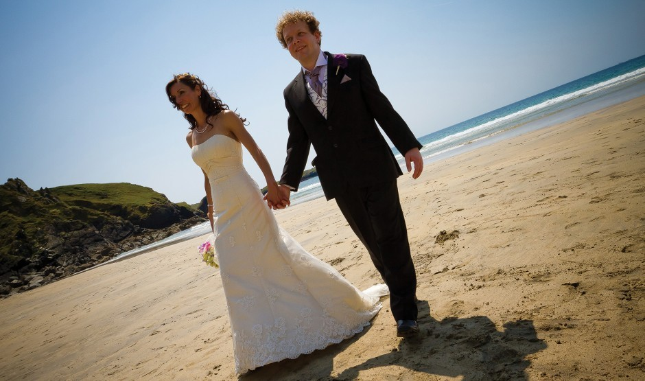 Couple on the beach after getting married at Polurrian Bay